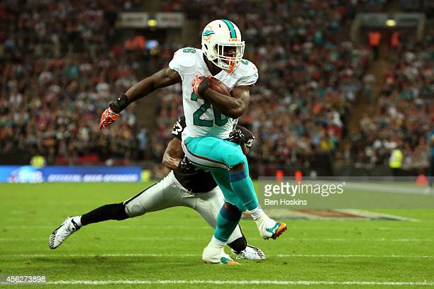 Lamar Miller of the Miami Dolphins scores his team's second touchdown on a nine yard rush during the NFL match between the Oakland Raiders and the...