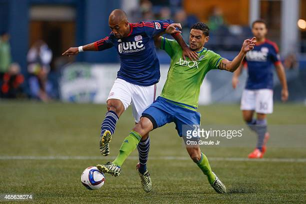 Lamar Neagle of the Seattle Sounders FC dribbles against Teal Bunbury of the New England Revolution at CenturyLink Field on March 8 2015 in Seattle...