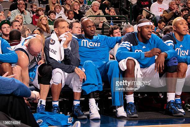 Lamar Odom Delonte West and Brendan Haywood of the Dallas Mavericks watch the action on the bench against the Oklahoma City Thunder on December 18...
