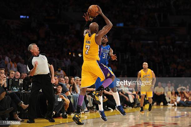 Lamar Odom of the Los Angeles Lakers shoots the ball from beyond half court as Jason Terry of the Dallas Mavericks is called for a foul by referee...