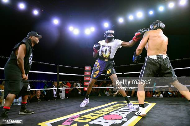 Lamar Odom punches Ojani Noa as special guest referee Bitcoin Rodney look on during the Heavyweight main event at the Celebrity Boxing Miami 2021...