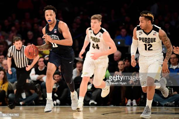 Lamar Stevens of the Penn State Nittany Lions is pursued by Isaac Haas and Vincent Edwards of the Purdue Boilermakers during the semifinals of the...