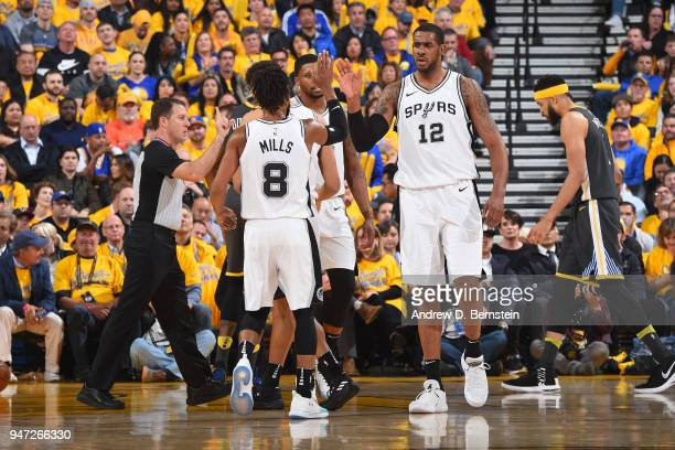LaMarcus Aldridge and Patty Mills of the San Antonio Spurs high five during the game against the Golden State Warriors in Game Two of Round One of...