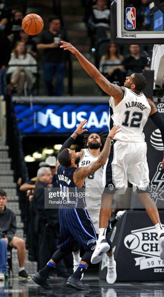 LaMarcus Aldridge #12 of the San Antonio Spurs blocks shot of D.J. Augustin #14 of the Orlando Magic at AT&T Center on March 13, 2018 in San Antonio, Texas.
