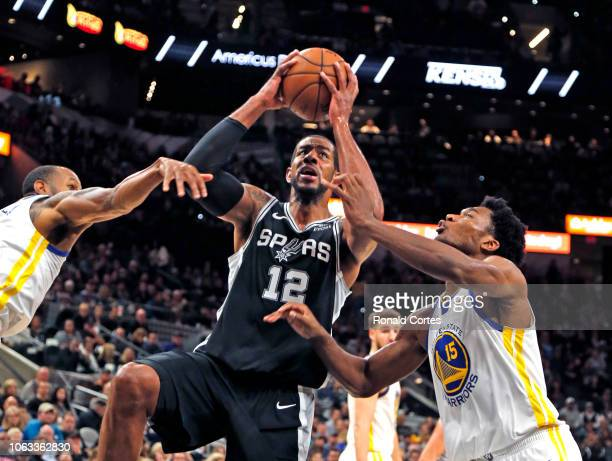 LaMarcus Aldridge of the San Antonio Spurs drives for two between Andre Iguodala of the Golden State Warriors and Damian Jones of the Golden State...