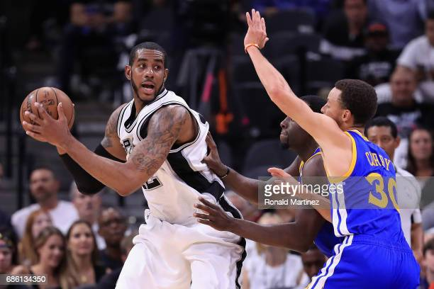LaMarcus Aldridge of the San Antonio Spurs handles the ball against Stephen Curry and Draymond Green of the Golden State Warriors in the first half...