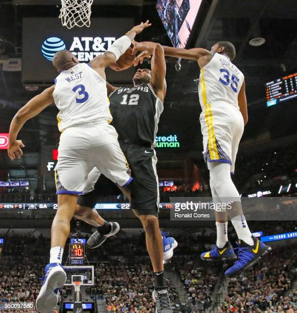 LaMarcus Aldridge of the San Antonio Spurs has his shot contested by David West and Kevin Durant of the Golden State Warriors in the first half of...