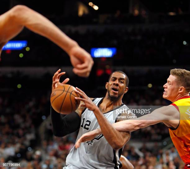 LaMarcus Aldridge of the San Antonio Spurs is fouled by Jonas Jerebko of the Utah jazz as he drives to the basket at ATT Center on March 23 2018 in...