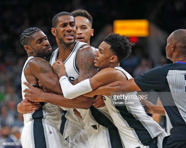 LaMarcus Aldridge of the San Antonio Spurs is held back by teammates Brandon Paul and Dejounte Murray after an altercation with Serge Ibaka of the...