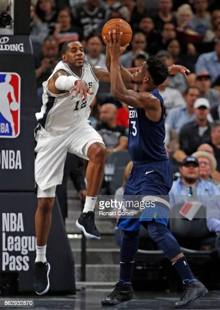 LaMarcus Aldridge of the San Antonio Spurs lunges at Jimmy Butler of the Minnesota Timberwolves at ATT Center on October 18 2017 in San Antonio Texas...