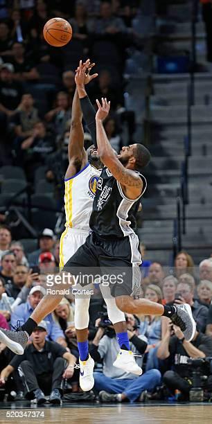 LaMarcus Aldridge of the San Antonio Spurs shoots over Draymond Green of the Golden State Warriors at ATT Center on April 10 2016 in San Antonio...