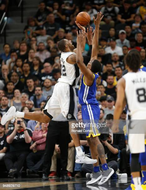 LaMarcus Aldridge of the San Antonio Spurs tries to shoot over Kevon Looney of the Golden State Warriors at ATT Center on April 19 2018 in San...