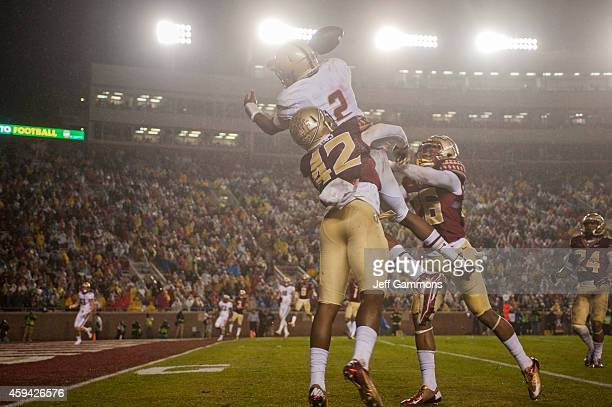 Lamarcus Brutus and PJ Williams of the Florida State Seminoles defend against a trick play with Quaterback Tyler Murphy of the Boston College Eagles...