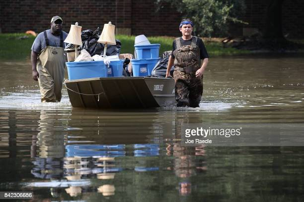 LaMarcus McCray and Allan Sommer pupsh a boat through a flooded neighborhood as they help bring items out of a friends home in an area where a...