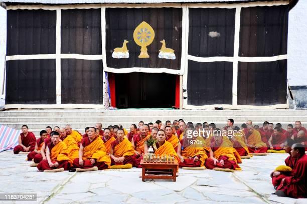 ラマスは、中国・甘粛省ガナン自治州クル県クル県のチベット仏教のラングムシ修道院のメインホールで祈る準備ができています。 - 甘粛省 ストックフォトと画像