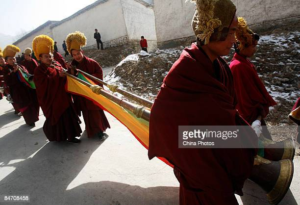 Lamas blow long trumpet on their way to send evil spirits which have been 'killed' during the 'Tiaoqian' praying ceremony at the Youning Temple on...