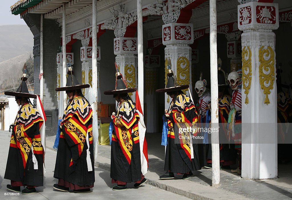 Lamas wait to dance during the 'Tiaoqian' praying ceremony at the Youning Temple on February 8, 2009 in Huzhu County of Qinghai Province, China. The Youning Temple holds the annual 'Tiaoqian' ceremony in the first lunar month each year. During the ceremony, monks will wear colourful traditional clothes and masks, performing the 'Fawang Dance' and 'Horse-headed Warrior Dance' to scare away evil spirits. Pilgrims also pray for good luck during the ceremony.