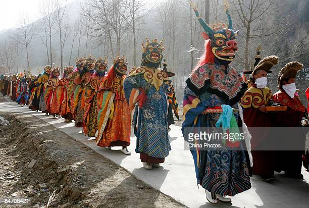 Lamas walk on a road to send evil spirits which have been 'killed' during the 'Tiaoqian' praying ceremony at the Youning Temple on February 8 2009 in...