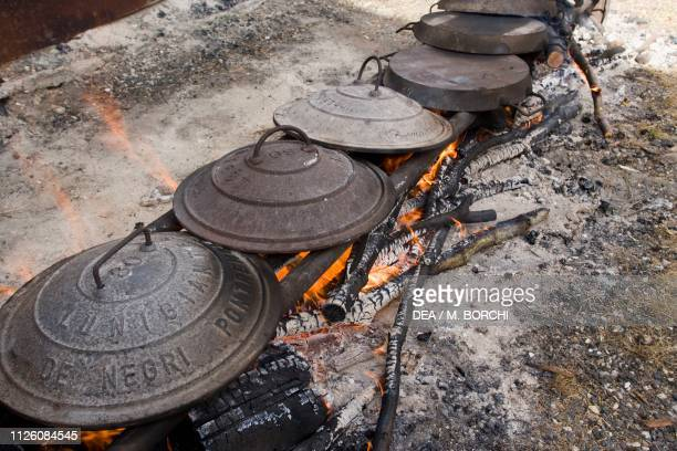 Lamb cooked in the testi traditional cast iron pans during Festival of zerasca sheep Canonica Zeri Lunigiana Tuscany Italy