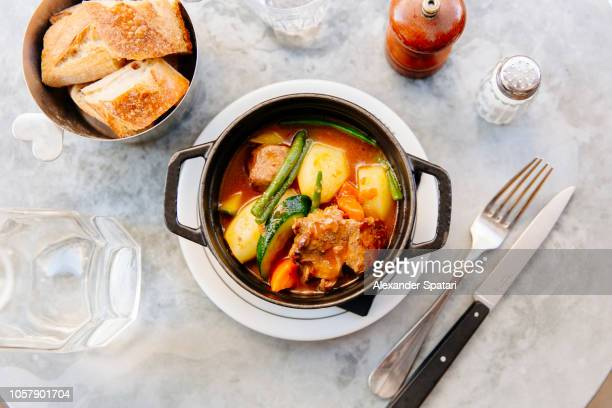lamb stew (navarin) with vegetables served in black cast iron casserole, high angle view - jour photos et images de collection