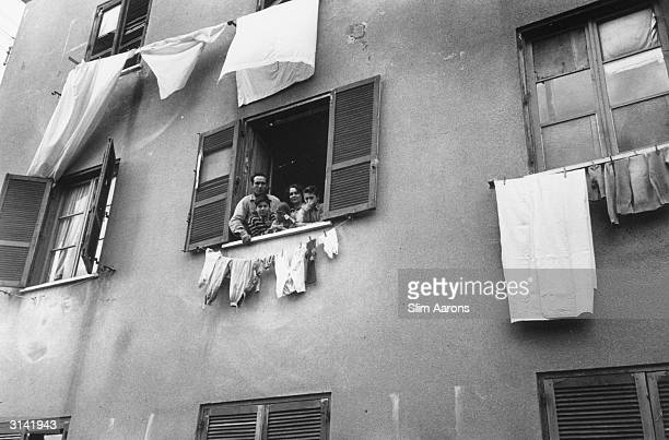 Lamberto Maggiorani star of Vittorio de Sica's film 'The Bicycle Thief' with his wife Giuseppina and children framed in the window of their flat in...