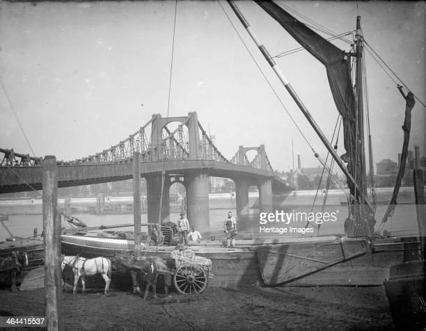 Lambeth Suspension Bridge, Lambeth, Greater London, c1860-c1922. The bridge, constructed across the River Thames in 1861-2, with a crane unloading...