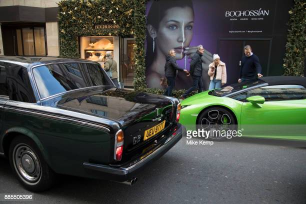 Lamborghini supercar is passed by a vintage predecessor Rolls Royce on Bond Street in London, England, United Kingdom. Cars like this are often seen...