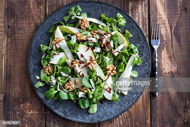 Lambs lettuce with pear, gorgonzola and walnut on plate, fork