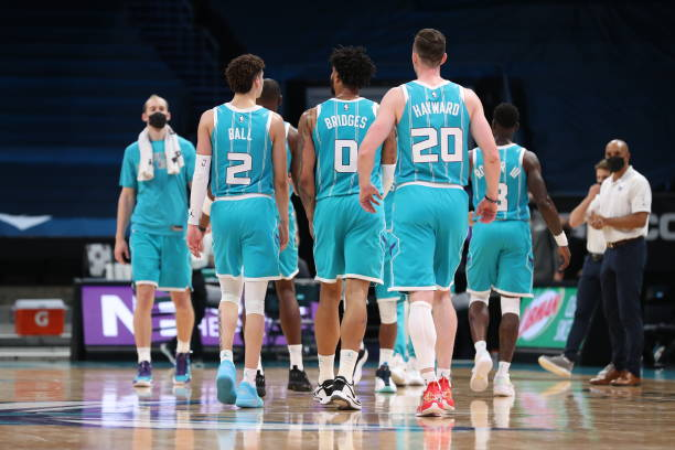 LaMelo Ball, Miles Bridges, and Gordon Hayward of the Charlotte Hornets looks on during the game against the Minnesota Timberwolves on February 12,...