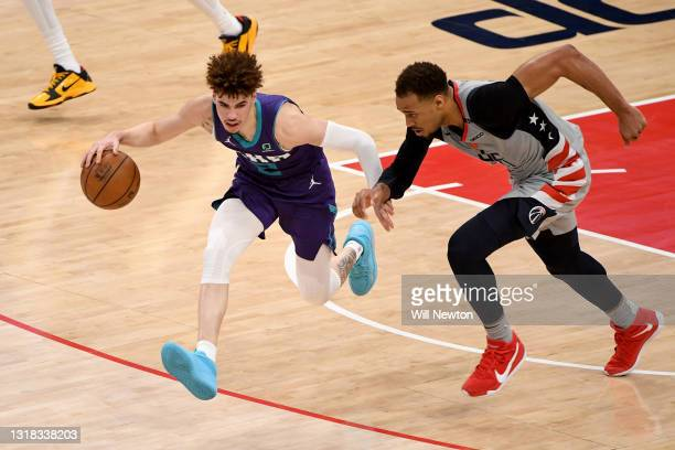 LaMelo Ball of the Charlotte Hornets dribbles in front of Daniel Gafford of the Washington Wizards during the second half at Capital One Arena on May...