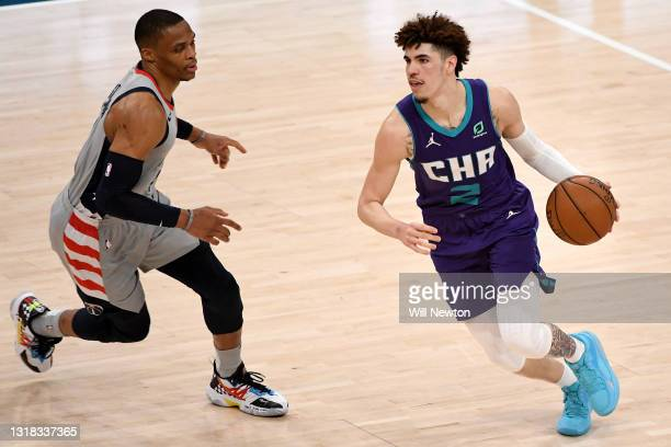 LaMelo Ball of the Charlotte Hornets dribbles in front of Russell Westbrook of the Washington Wizards during the second half at Capital One Arena on...