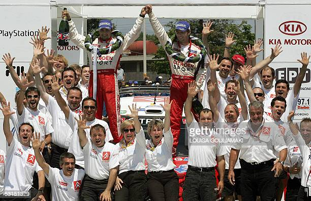 World Champion Sebastien Loeb of France and his codriver Daniel Elena of MonteCarlo celebrate with the Citroen rally team 26 June2005 their victory...