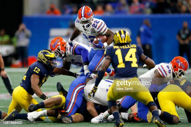 Lamical Perine of the Florida Gators carries the ball against the Michigan Wolverines in the first quarter during the ChickfilA Peach Bowl at...