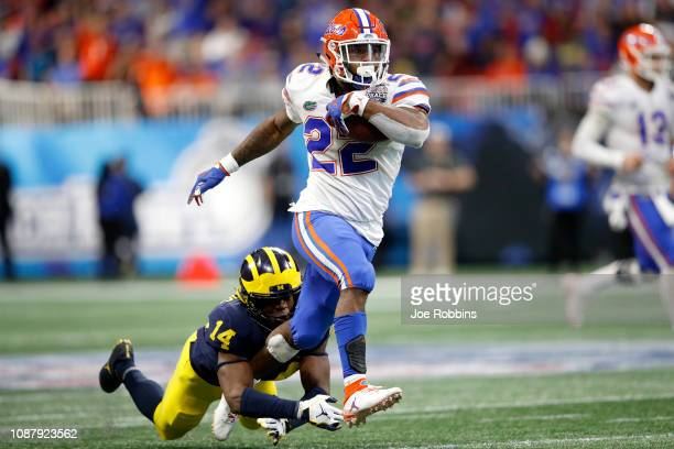 Lamical Perine of the Florida Gators escapes the tackle attempt of Josh Metellus of the Michigan Wolverines and runs for a fourth quarter touchdown...