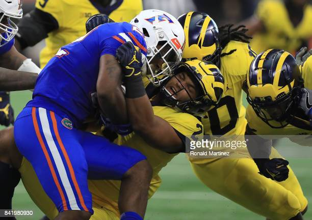 Lamical Perine of the Florida Gators gets pulled down by Carlo Kemp of the Michigan Wolverines in the first half of a game at ATT Stadium on...