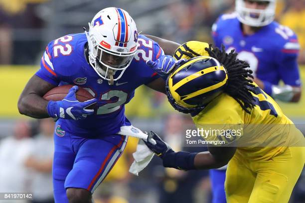 Lamical Perine of the Florida Gators holds off Devin Bush of the Michigan Wolverines on a carry in the second quarter of a game at ATT Stadium on...