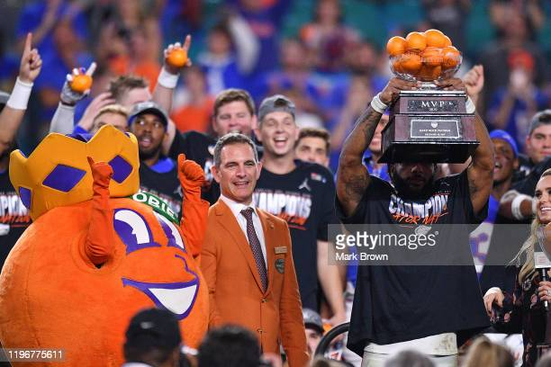 Lamical Perine of the Florida Gators raises the MVP trophy after winning the Capital One Orange Bowl against the Virginia Cavaliers at Hard Rock...