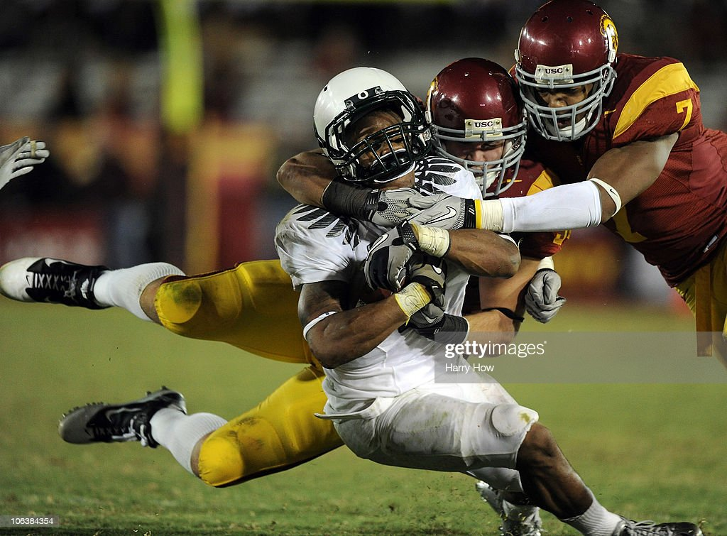 LaMichael James #21 of the Oregon Ducks takes a hit from Chris Galippo and T.J. McDonald #7 of the USC Trojans during the fourth quarter at Los Angeles Memorial Coliseum on October 30, 2010 in Los Angeles, California.