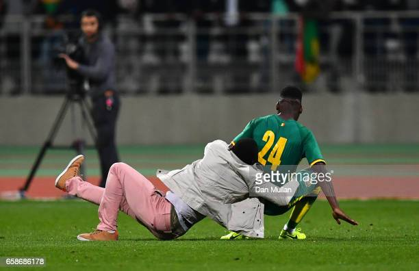 Lamine Gassama of Senegal is tackled to the ground by a pitch invader during the International Friendly match between the Ivory Coast and Senegal at...