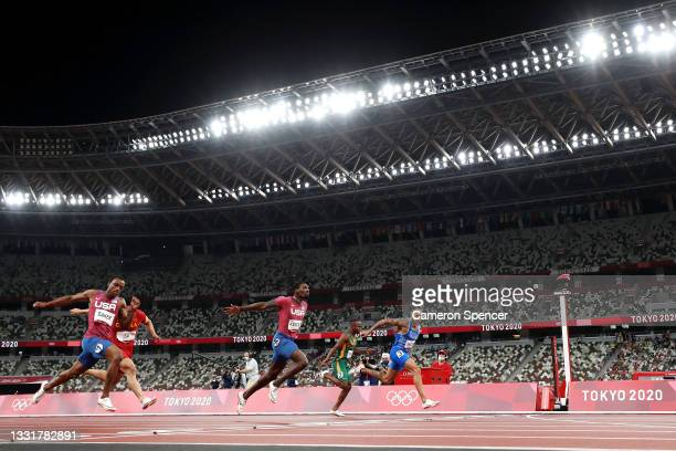 Lamont Marcell Jacobs of Team Italy crosses the finish line ahead of Fred Kerley of Team United States in the Men's 100m Final on day nine of the...