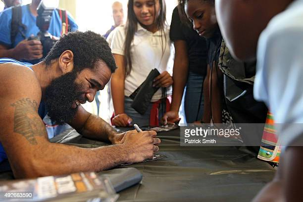 Lamont Peterson signs autographs for children from the Boys and Girls Club during fighter media workouts in the Alexandria Boxing Club at the Charles...