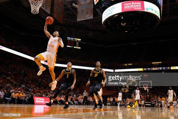 Lamonte Turner of the Tennessee Volunteers dunks the ball in front of Xavier Pinson of the Missouri Tigers and Torrence Watson of the Missouri Tigers...