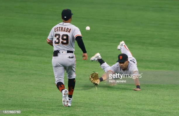 LaMonte Wade Jr of the San Francisco Giants dives for a ball off the bat of Adolis Garcia of the Texas Rangers as Thairo Estrada of the San Francisco...