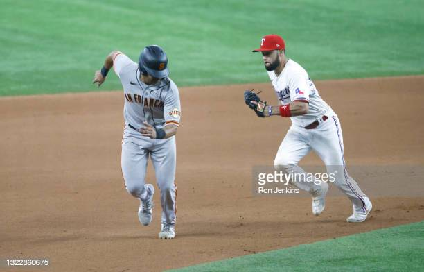 LaMonte Wade Jr of the San Francisco Giants is caught and tagged out by Isiah Kiner-Falefa of the Texas Rangers during the eleventh inning at Globe...