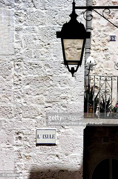 lamp and whitewashed wall - cisternino stock photos and pictures