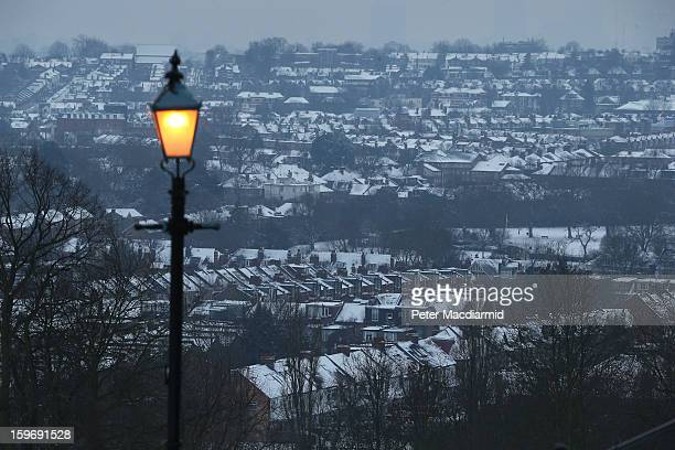 A lamp illuminates the view of snow covered houses near Alexandra Palace on January 18 2013 in London England Severe weather is expected in parts of...