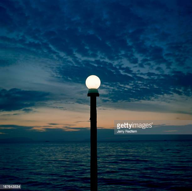 A lamp is competing with the sunset over the Gulf of Thailand as seen from a guesthouse at Kep Kep was once the weekend getaway place for the French...