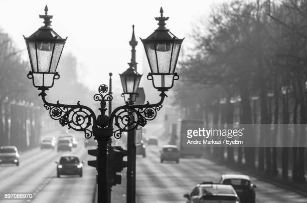 Lamp Posts Amidst Street In City