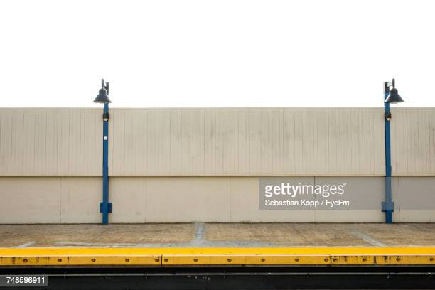 lamp posts by wall at railroad station platform against clear sky - railroad station platform stock pictures, royalty-free photos & images