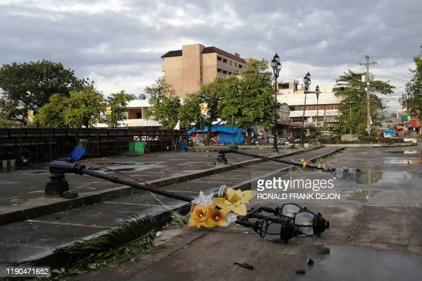 TOPSHOT Lamp posts damaged due to typhoon Phanfone lie on a road in Ormoc City Leyte province in central Philippines on December 25 2019 Typhoon...